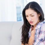 Woman coughing in pain: Lorenzo & Lorenzo Personal Injury Blog