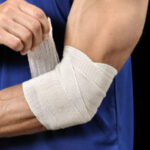 Man bandaging arm: Lorenzo & Lorenzo Personal Injury Blog
