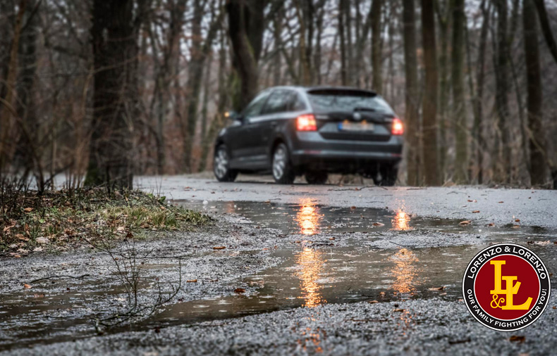 Puddle on road during storm with car in background