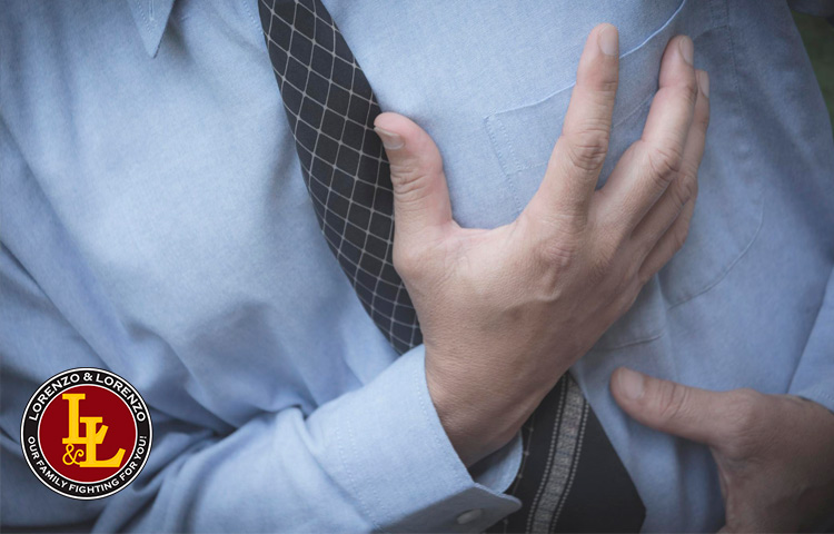 man having a heart attack clutches his chest
